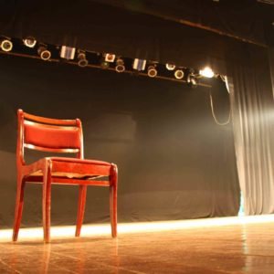 Image of a red chair on a stage for the What is a broad creative arts curriculum? post